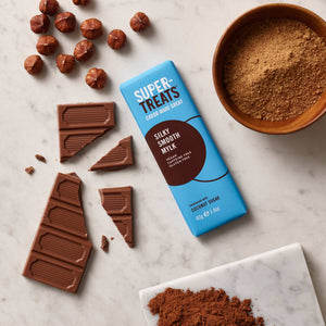 Supertreats Silky Smooth Mylk carob chocolate bar surrounded by pieces of carob chocolate, carob powder and coconut sugar