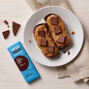 Toast slices topped with peanut butter and pieces of carob chocolate next to a Supertreats Silky Smooth Mylk carob bar