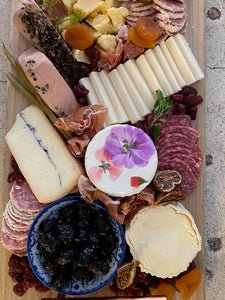cheese and charcuterie board with assorted cheeses, olives and meats.