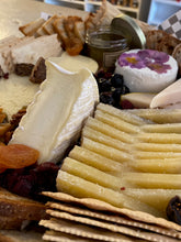 Load image into Gallery viewer, close up of cheese and charcuterie board with assorted cheeses, breads and meats.