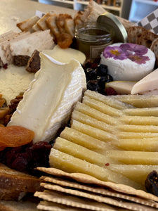close up of cheese and charcuterie board with assorted cheeses, breads and meats.
