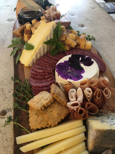 cheese and charcuterie board with assorted cheeses, breads and meats.