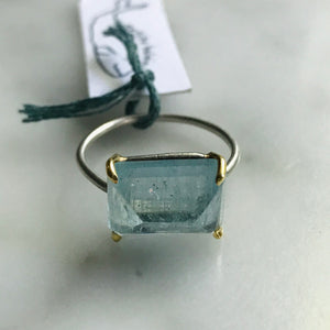 aquamarine set in 18k gold prongs with silver band