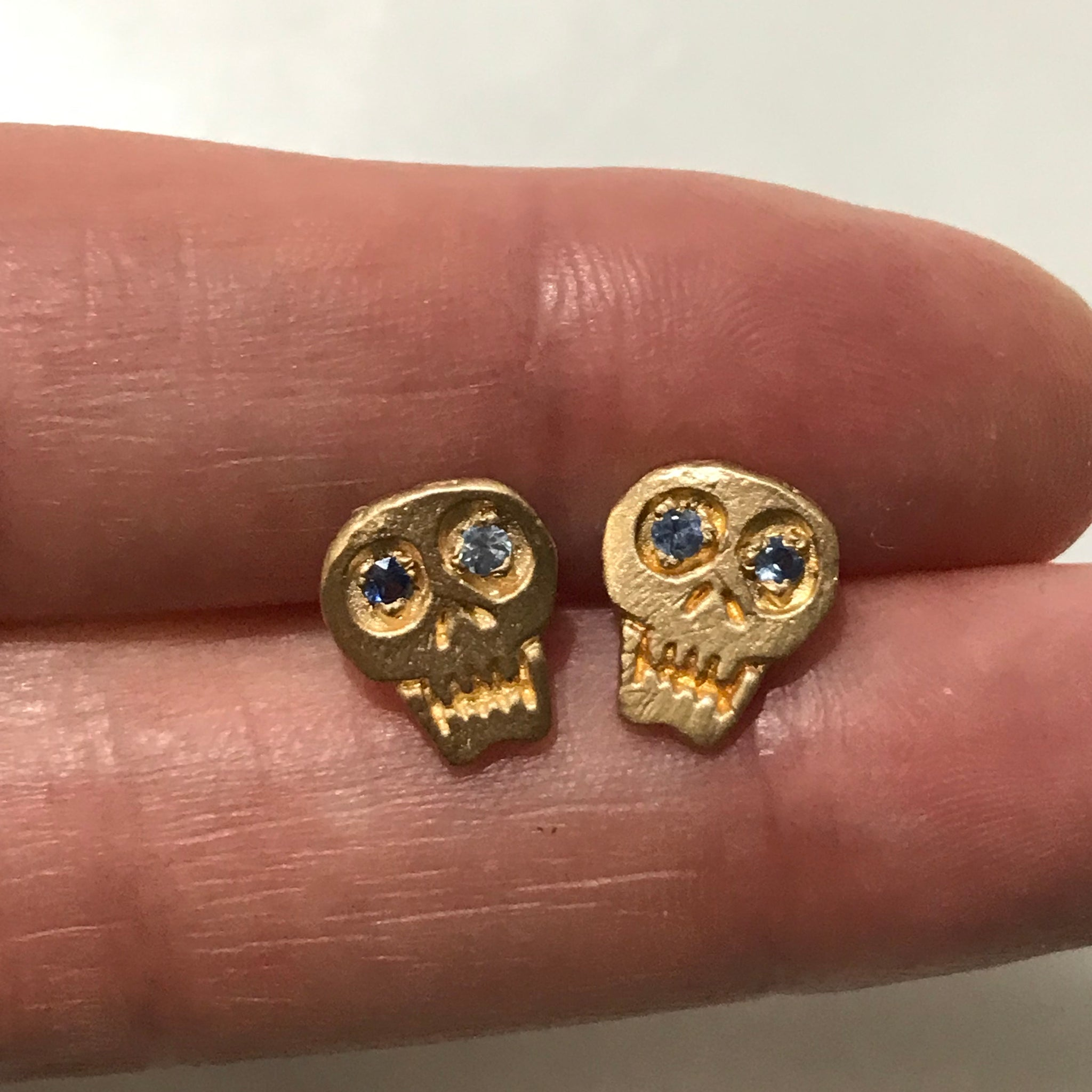 hand carved 18k gold skull earrings with sapphire eyes