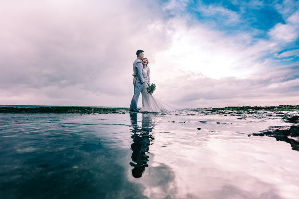 A married couple having a photograph on a beach during their wedding ceremony - Tim Downer Celebrant