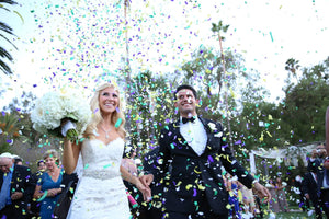 A couple who have just been married and the guests are throwing confetti over them as good luck - Tim Downer Celebrant