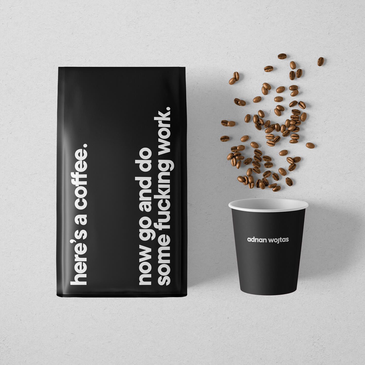 Black bag of whole bean specialty coffee accompanied by a black eco friendly coffee cup with a handful of lightly roasted specialty coffee beans.