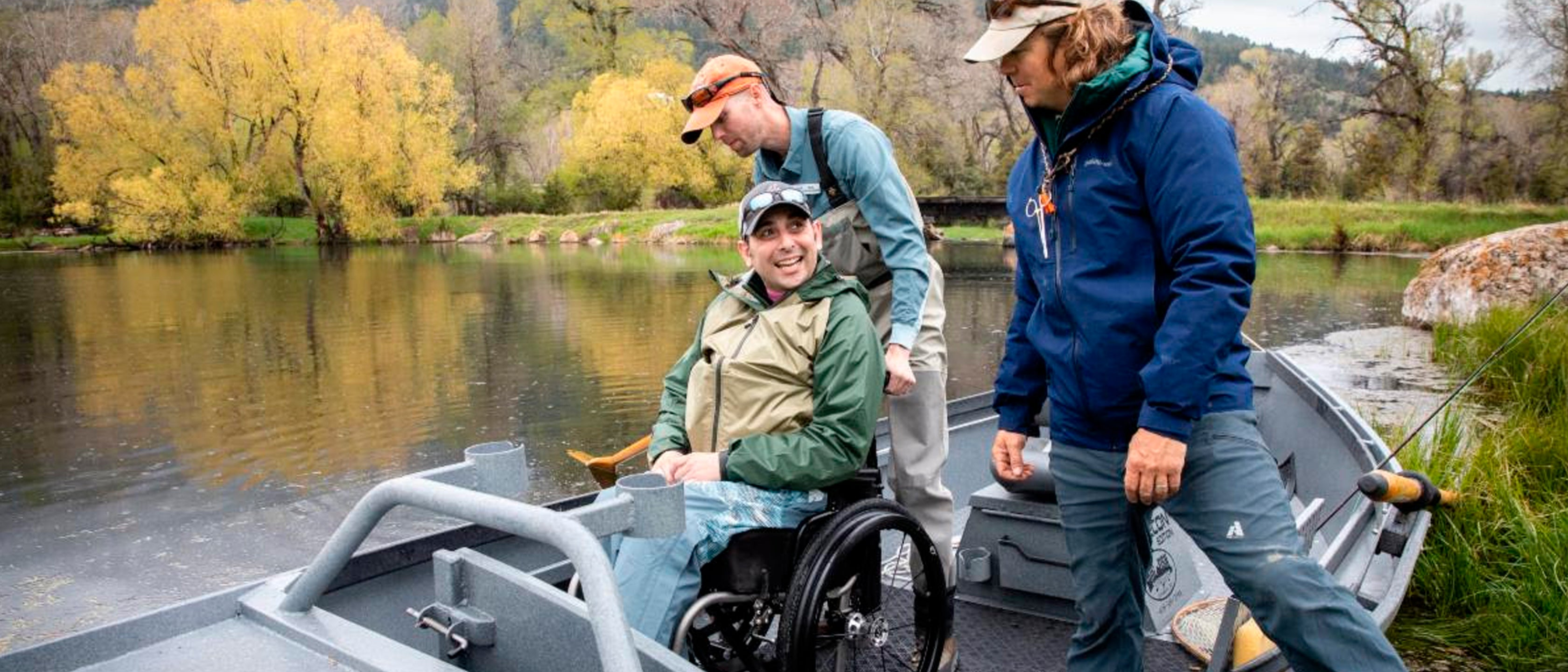 warriors and quiet waters helping vet in wheelchair get in boat