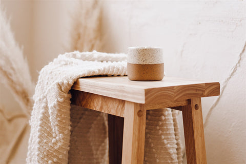 soy candle in a ceramic pot on a wooden bench