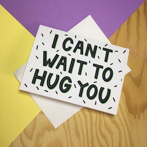 "card reads ""I can't wait to hug you"" in bold black letters with white and green detailing"