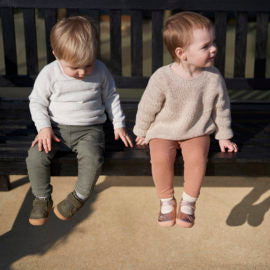 Two kids on bench with shoes