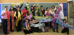 Image of Mila Lansdowne's silk painting class with participants showing their creations.