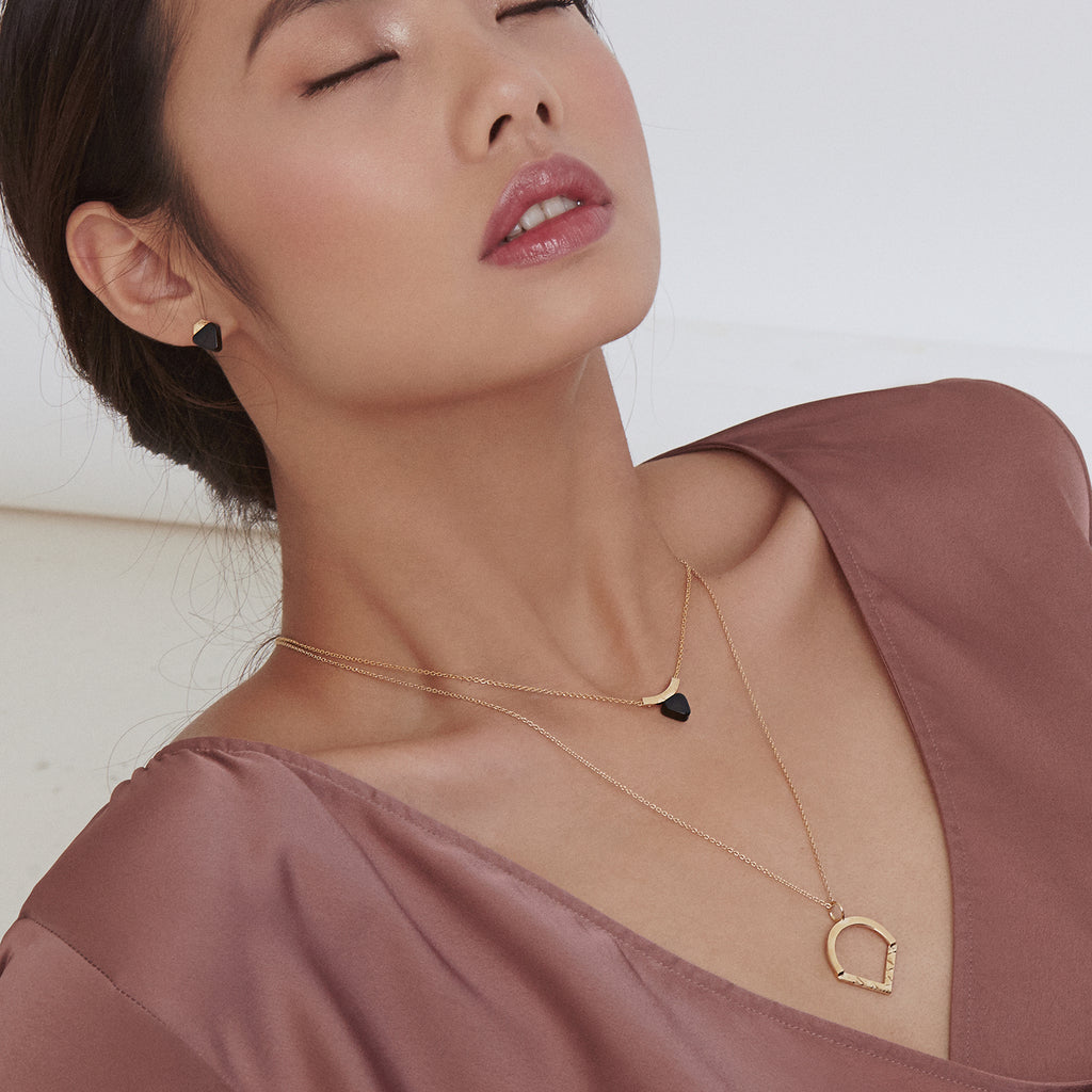 Layered onyx curved bar necklace and geometric necklace in gold
