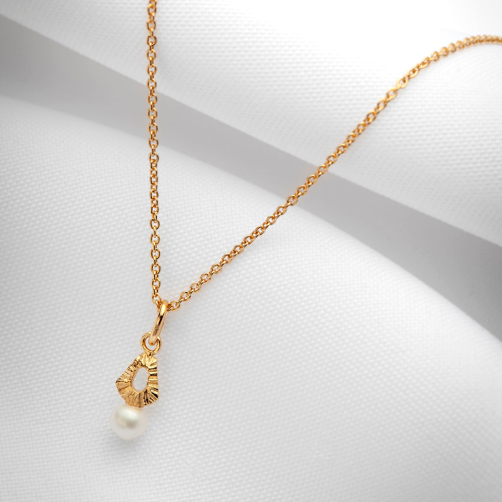 Gold plated charm necklace with small freshwater pearl