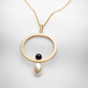 Gold oval pendant on long chain with black onyx and big pearl