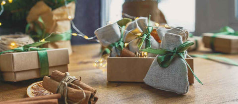 Christmas presents wrapped in sustainable kraft paper wrap and Furoshiki, tied with green ribbon
