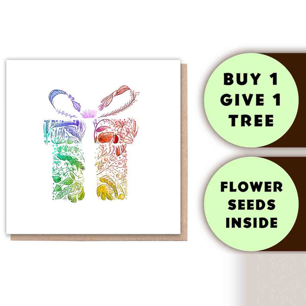 "An image of a gift wrapped box in rainbow colours but when you look closely the image is made up from different coloured nature elements, including leaves and ferns. Also there are text boxes, one says ""Buy 1 Give 1 tree"" the other days ""Flower seeds inside"""