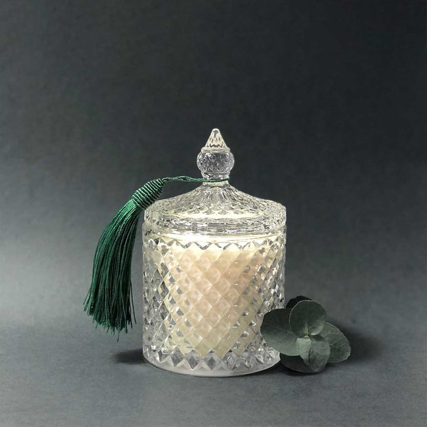 A beautiful candle presented in a crystal candle holder with a green tassel.