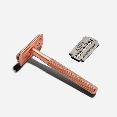 A rose gold reusable safety razor with razor blades next to it