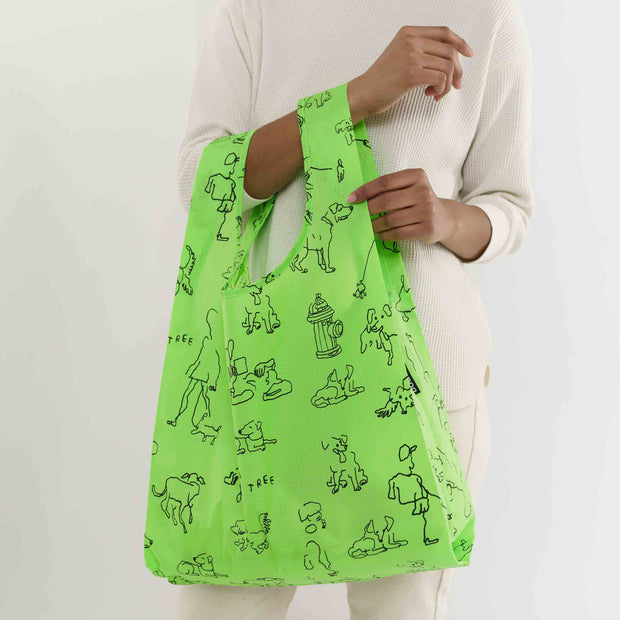A bright green Baggu brand reusable bag, featuring simple black line drawings of various dogs and their owners. Held from the arm of a person wearing all while clothing.