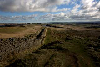 Colour landscape image of fluffy white clouds and pathway at Hadrian's Wall.