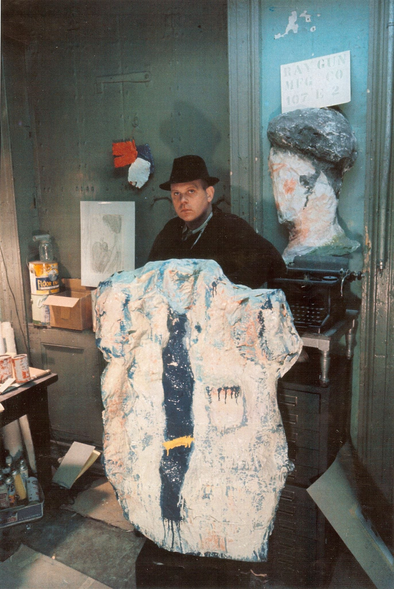 Claes Oldenburg (1929- ) with White Shirt with Blue Tie Ray Gun Mfg. Co. Studio, 107 East 2nd Street, New York, 1965 Default Title