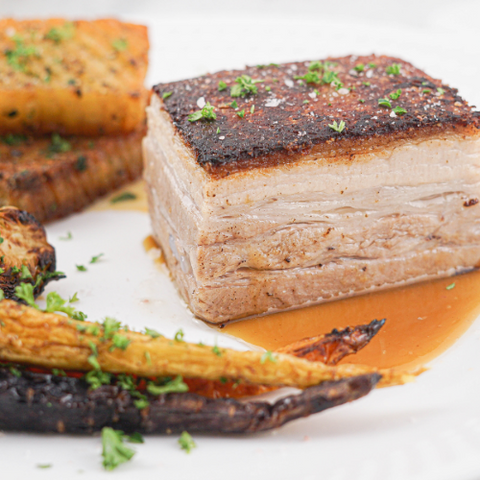 Crispy pork belly piece plated on cider jus with a side of roasted carrot, sprouts and accordion potatoes