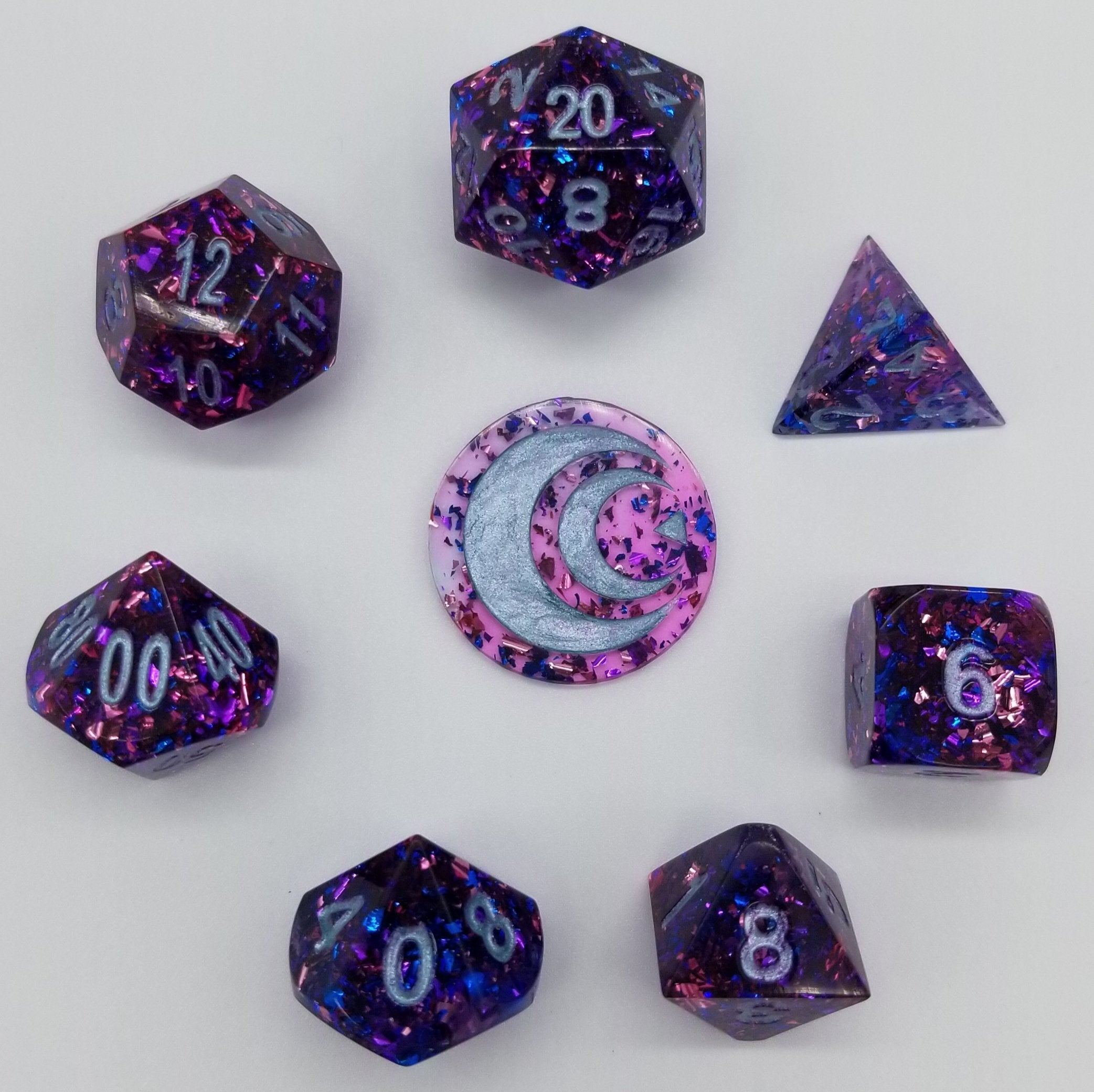 Transparent purple handmade resin dice with multicolored metallic foil inside and light blue ink.