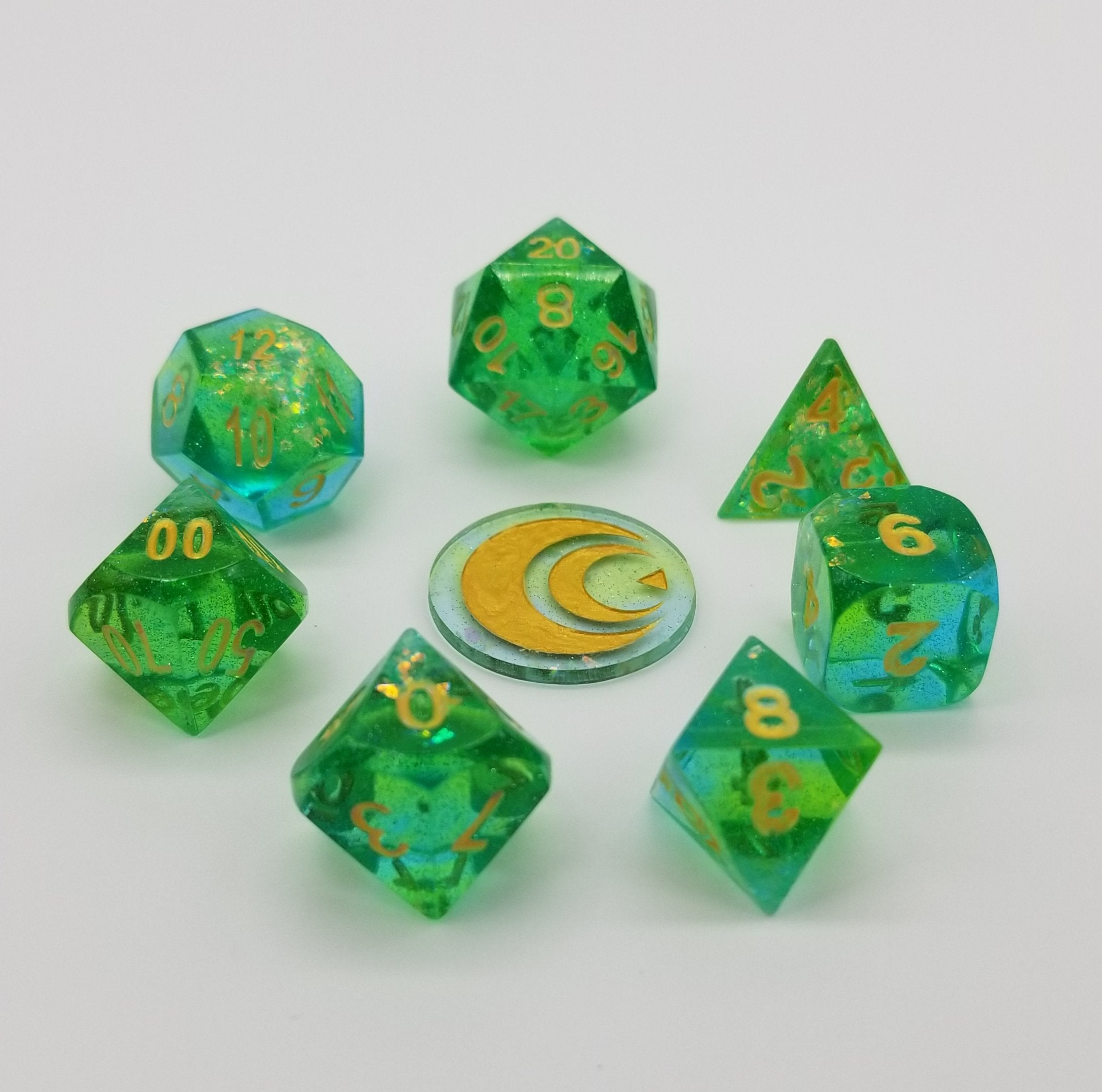 Transparent green handmade resin dice with incandescent Mylar flakes inside and gold ink.