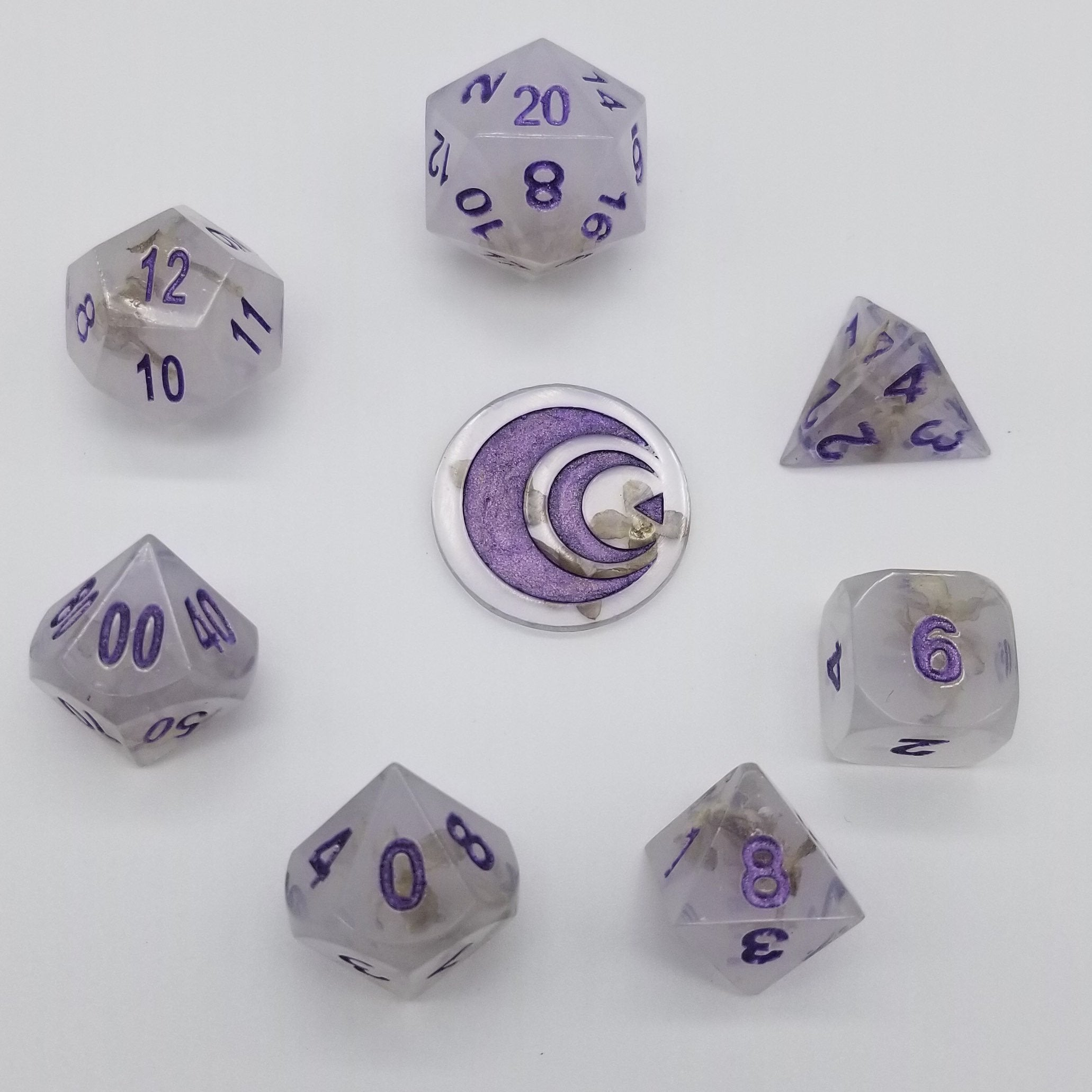 Semi-opaque handmade resin dice with lilac flowers embedded inside and purple ink.