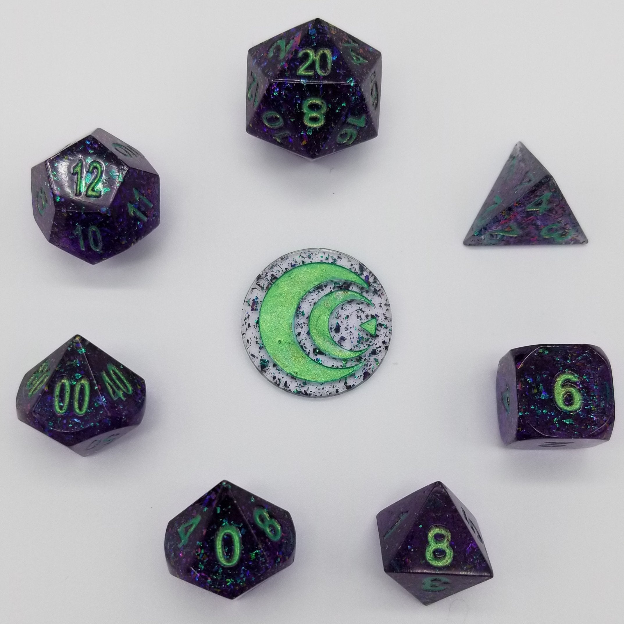 Handmade transparent dark purple resin dice with green-purple shift flakes inside and green ink.