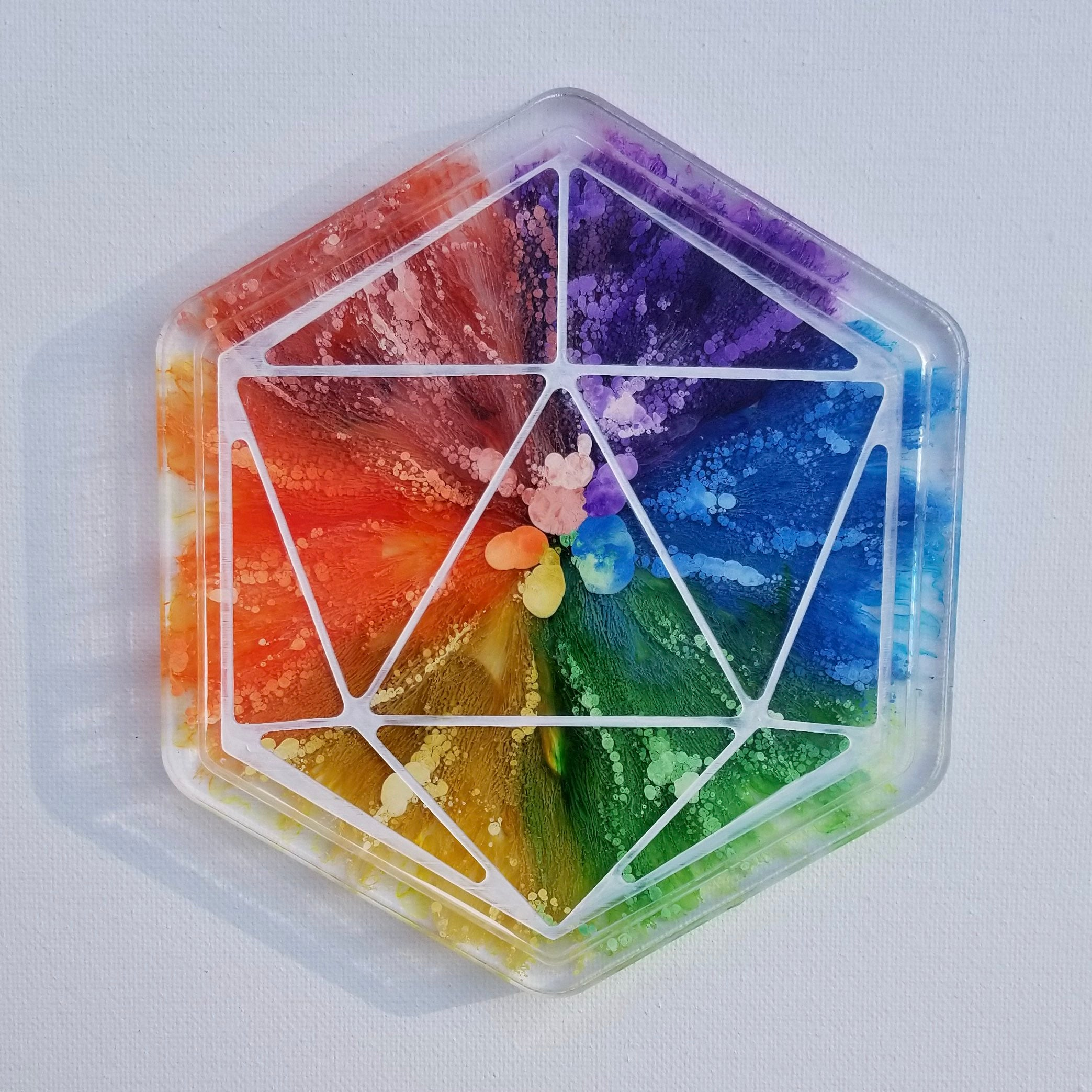 This is a handmade rainbow dice rolling tray with white ink. The rainbow colors look like sea anemones encased in clear resin.
