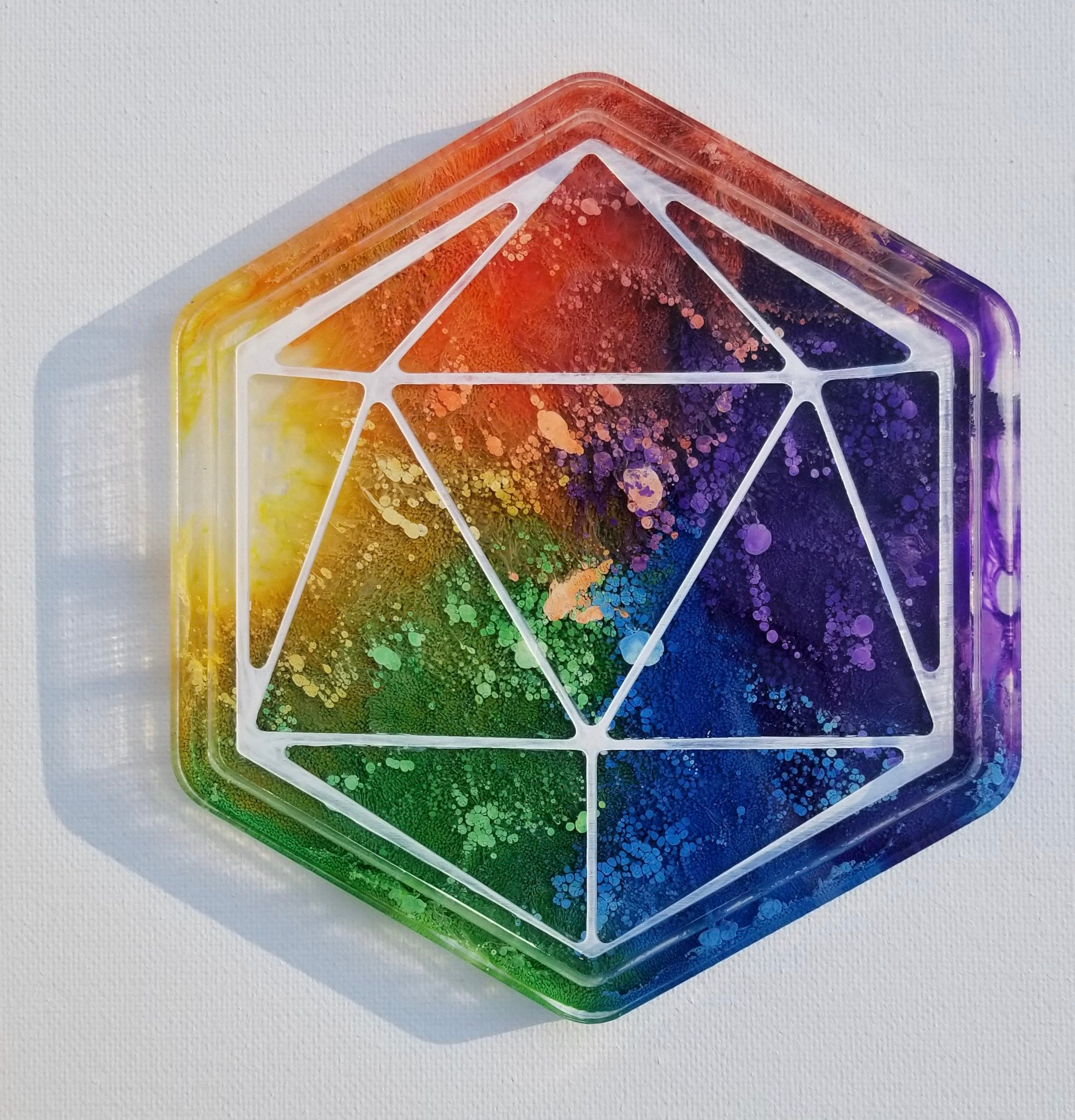 This is a handmade rainbow dice rolling tray with white ink. The rainbow colors look like sea anemone encased in clear resin.