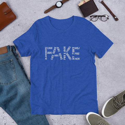 "The word ""FAKE"" lays across the middle of the shirt. Each character of the word is constructed using news network names. For example, the ""F"" has ""Bloomberg"" as the stem with ""CNN"" as the top prong and ""BBC"" as the prong in the middle of the word ""Bloomberg"""