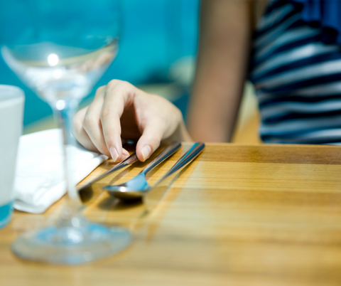 woman sitting at table with wine glass
