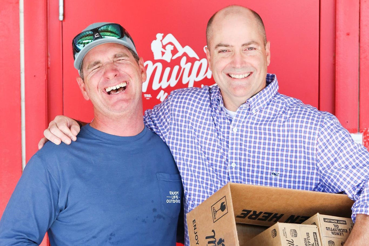 two males hugging and laughing in front of red door at murphys naturals warehouse