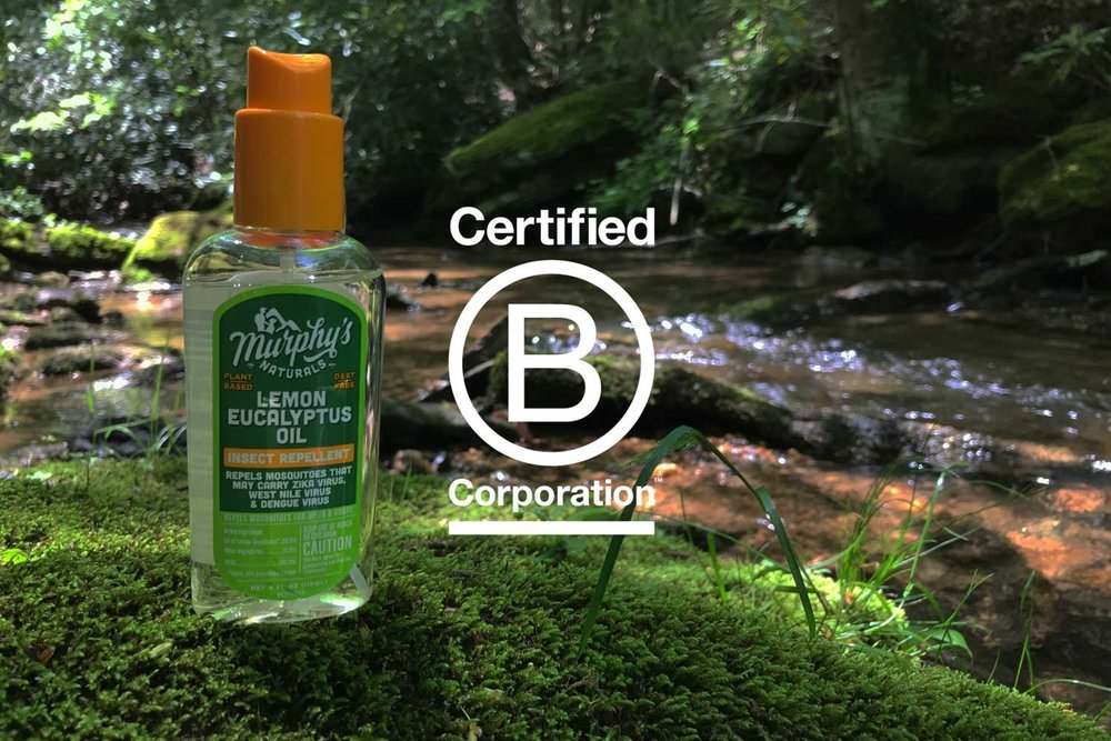 bottle of lemon eucalyptus oil mosquito spray sitting on mossy rock by river
