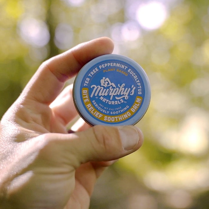 Load and play video in Gallery viewer, video of male using murphys naturals bite relief soothing balm while hiking in the woods