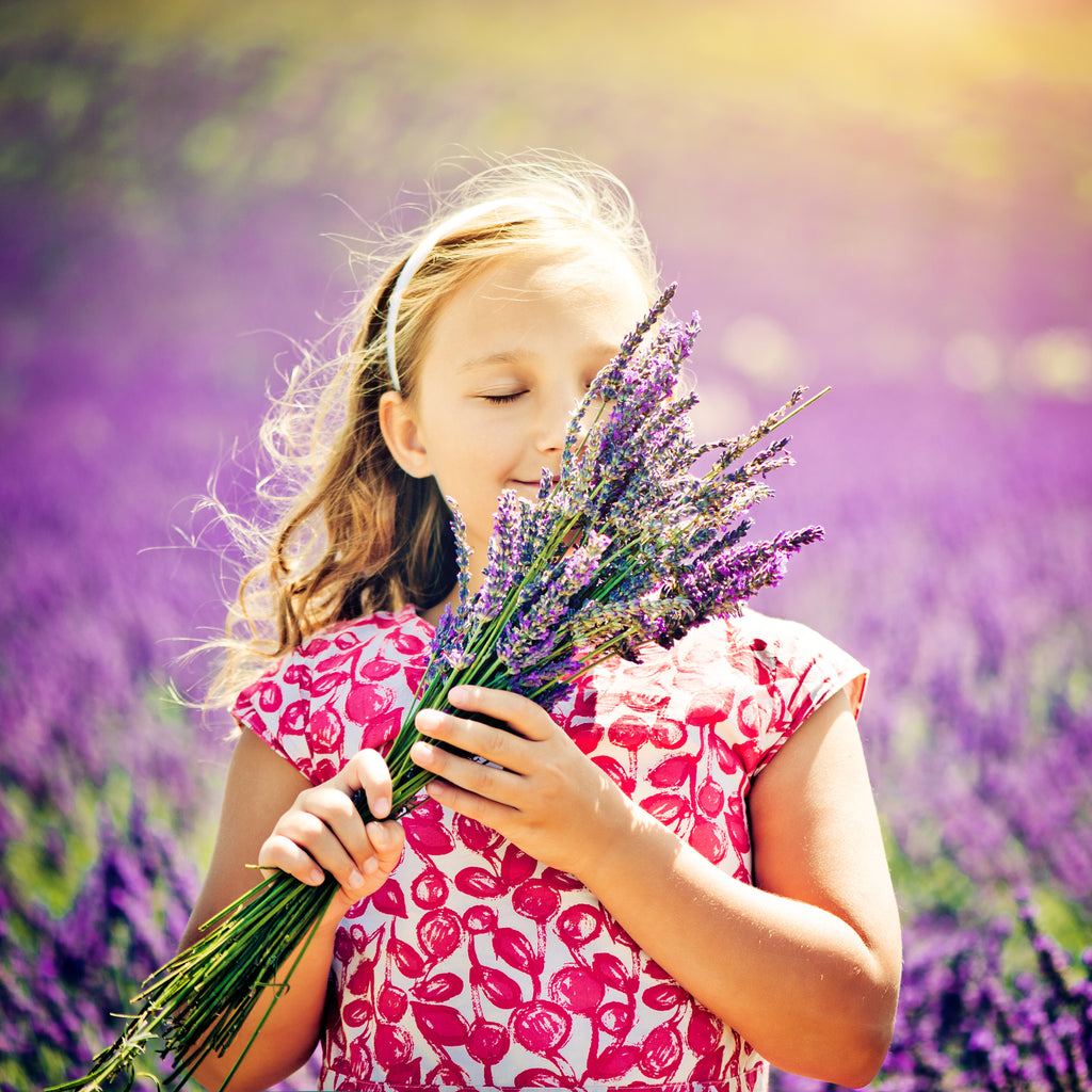 Young girl smelling lavender