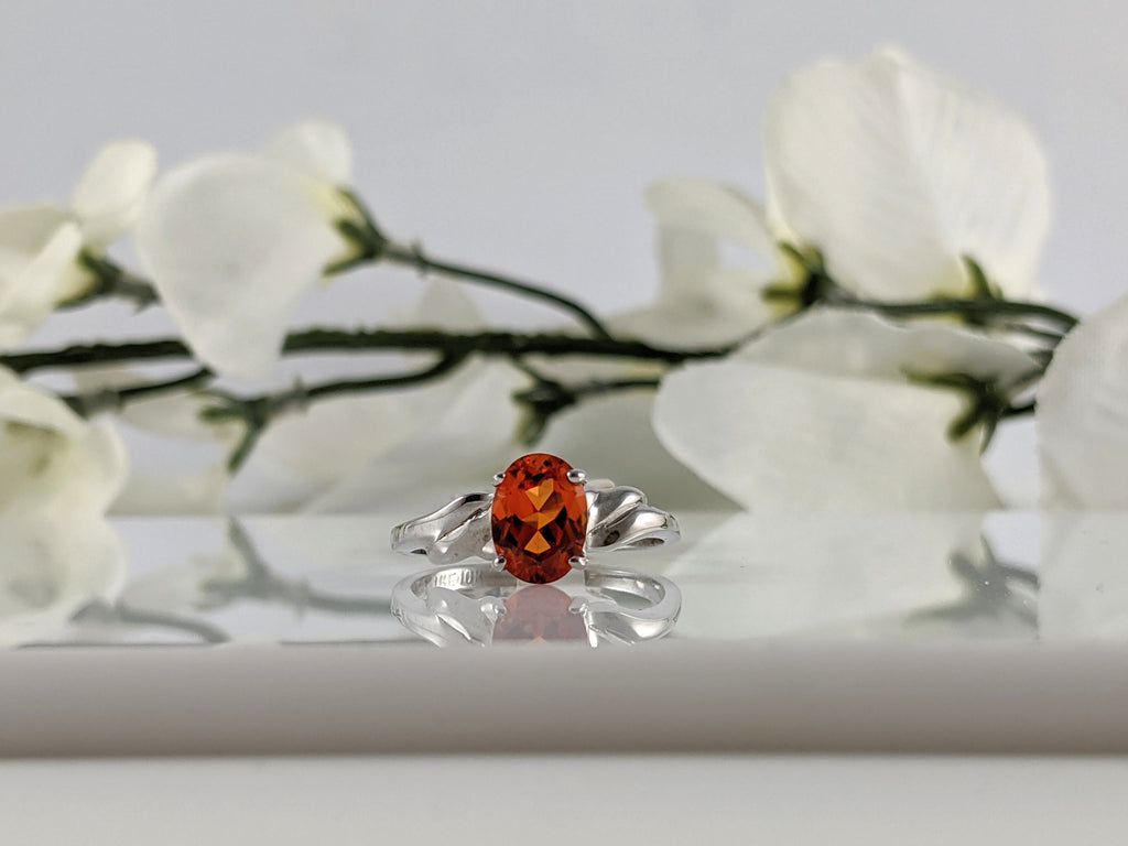 Classic simple setting holding an 8x6mm oval created orange sapphire. 10L white gold. Finger size 6. $415.00
