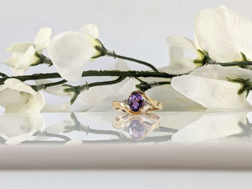 Constructed of 14K yellow gold this lovely ring features a 7x5mm oval amethyst and .03cttw in round brilliant cut diamonds. Simple and elegant. Finger size 7. $295.00