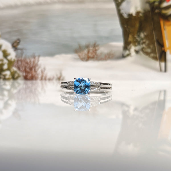 10K white gold and swiss blue topaz ring. Ring is set with a cushion cut 5x5mm topaz. .20cttw in round brilliant cut diamonds compliment this beautiful piece. Finger size 6.75. $990.00