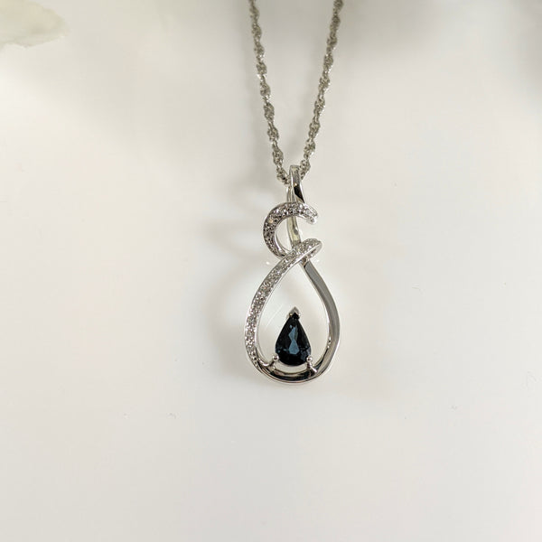"This fabulous pendant is constructed of 14K white gold and contains a lovely 6x4mm blue Sapphire. Complimenting this stone are .10cttw in round brilliant cut diamonds. This pendant is long, measuring 28.00mm long and is hung an a 20"" inch 14k white gold Singapore chain. $1050.00"