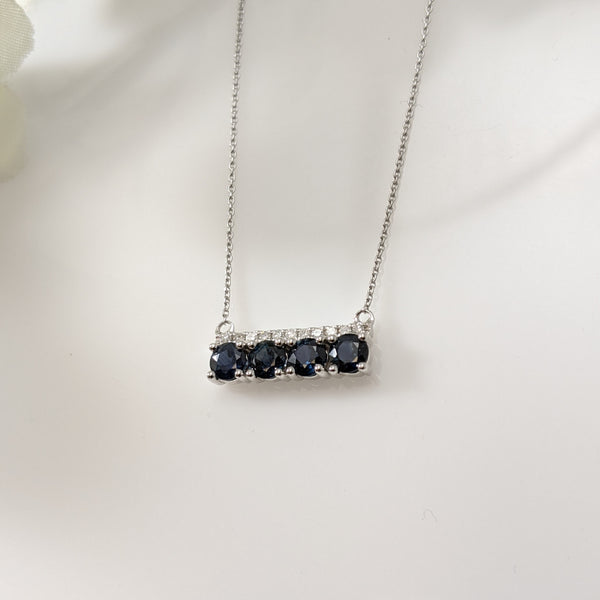 "If you are a fan of the bar necklaces, this is the necklace for you! Both contemporary and elegant this stunning necklace is set with four round natural blue Sapphires and 1/20th carats of diamond. Pendant measures 14.50mm horizontally. Comes with the chain. 10k white gold. 18"" inches. $550.00"