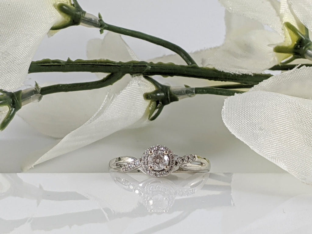 Fancy and affordable this 10k white gold and diamond engagement ring contains a .22ct center diamond and .11cttw in additional accent diamonds. Finger size 7. $750.00