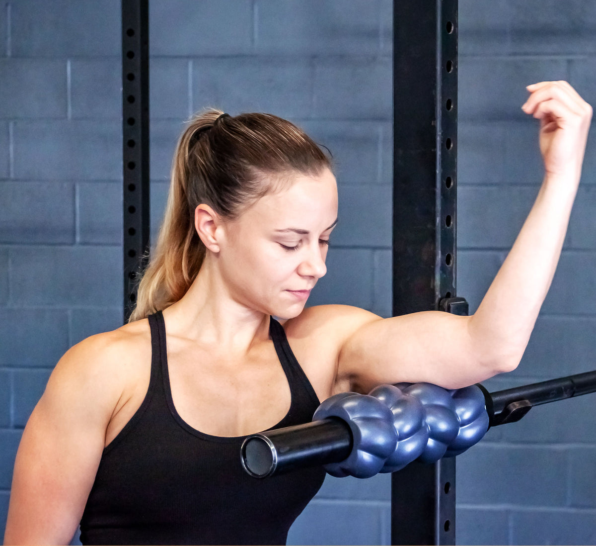 A fit woman rolling her triceps muscles with a barbell roller in a squat rack.
