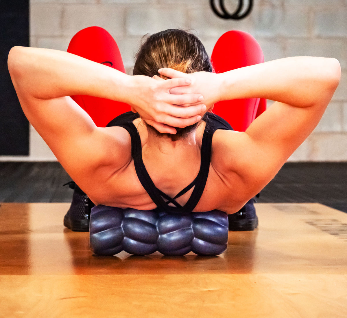 Athletic woman using the Barbell Roller to roll her upper back