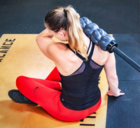 Athlete using a foam roller that fits on a barbell to massage the upper trapezius muscles