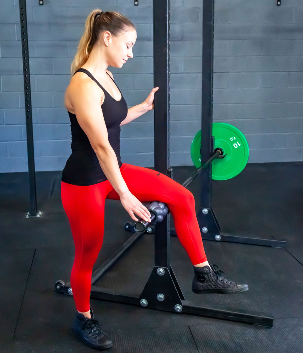The Revolv Barbell Roller alleviates muscle tension when mounted on a barbell in a rack.