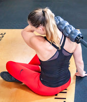 A woman is using a barbell as a weighted handle for the barbellroller to relax the upper triceps.